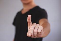 Een jonge kerel in een zwarte t-shirt die op het scherm drukt Op grijze B Royalty-vrije Stock Afbeelding