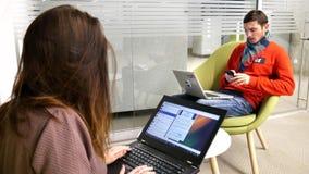 Een jonge kerel en een meisje zitten bij laptop stock footage