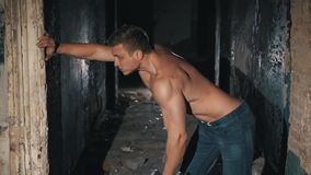 Een jonge kerel gaat binnen voor sporten in een donkere, verbrijzelde ruimte onder zoeklichten stock footage