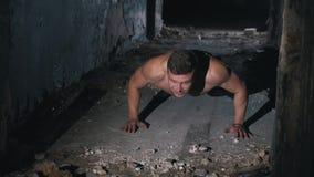 Een jonge kerel gaat binnen voor sporten in een donkere, verbrijzelde ruimte onder zoeklichten stock video