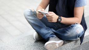 Een jonge kerel gebruikt zijn smartphone terwijl het zitten op het asfalt royalty-vrije stock foto's