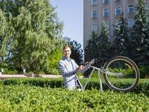 Een jonge kerel heft zijn fiets op het rek in de tuin van het beleid op royalty-vrije stock afbeelding