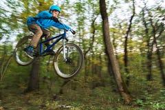 Een jonge kerel in een helmvliegen landde op een fiets na het springen van kicker Stock Foto
