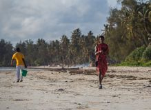 een jonge kerel helpt zijn vader en draagt dingen aan de boot Zeegezicht met mensen, boot en horizonlijn stock afbeelding