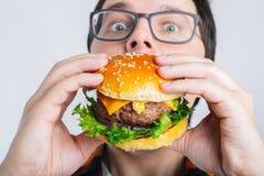 Een jonge kerel houdt een verse Hamburger Een zeer hongerige student eet snel voedsel Heet nuttig voedsel Het concept gulzigheid  royalty-vrije stock afbeelding