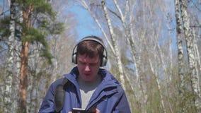 Een jonge kerel loopt in het Park, luisterend aan muziek door de hoofdtelefoons Ochtendgang in de verse lucht in de lente stock videobeelden