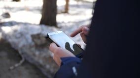 Een jonge kerel loopt onderaan de straat en gebruikt de telefoon voor Internet Close-up stock footage