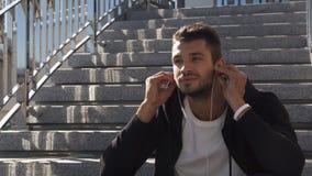 Een jonge kerel luistert aan muziek op hoofdtelefoons en geniet van de ochtend stock videobeelden