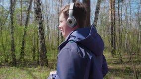 Een jonge kerel maakt een looppas in het park, luisterend aan muziek door de hoofdtelefoons Ochtendgang in de verse lucht in stock footage