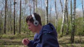 Een jonge kerel maakt een looppas in het park, luisterend aan muziek door de hoofdtelefoons Ochtendgang in de verse lucht in stock videobeelden
