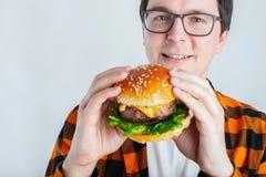 Een jonge kerel met glazen die een verse Hamburger houden Een zeer hongerige student eet snel voedsel Heet nuttig voedsel Het con stock afbeeldingen