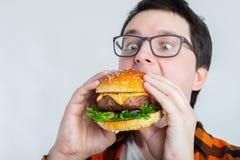 Een jonge kerel met glazen die een verse Hamburger houden Een zeer hongerige student eet snel voedsel Heet nuttig voedsel Het con stock foto
