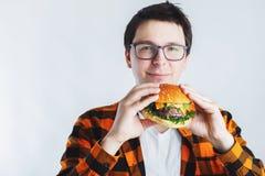 Een jonge kerel met glazen die een verse Hamburger houden Een zeer hongerige student eet snel voedsel Heet nuttig voedsel Het con royalty-vrije stock foto