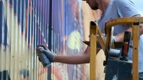 Een jonge kerel met a kan van verf trekt graffiti op de muur Één handclose-up stock videobeelden