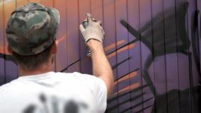 Een jonge kerel met a kan van verf trekt graffiti op de muur Één handclose-up stock video