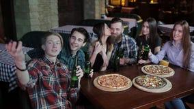 Een jonge kerel op zijn telefoon maakt tot een selfie vrolijk bedrijf in pizzeria stock videobeelden