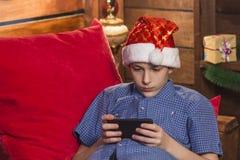 Een jonge kerel in een Santa Claus-hoed, in een blauw geruit overhemd, zit in de Nieuwjaar` s hoek, houdt zijn telefoon in zijn h royalty-vrije stock afbeelding