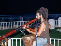 Een jonge kerel speelt een gitaar en een grote pijp in de avond op de waterkant in de stad van Nahariya, in Israël stock foto's