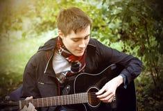 Een jonge kerel speelt een zwarte akoestische gitaar, zittend in het Park royalty-vrije stock afbeelding