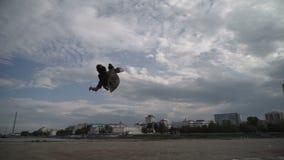 Een jonge kerel springt en doet een salto mortale stock videobeelden
