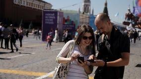 Een jonge kerel toont een jong meisje hoe te aan de juiste plaats dichtbij Rood Vierkant binnen te komen stock video