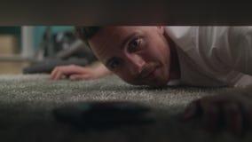 Een jonge kerel vindt een verloren portefeuille onder de bank in de woonkamer stock videobeelden