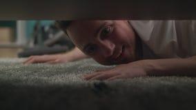Een jonge kerel vindt een verloren sleutelbos onder de bank in de woonkamer stock video