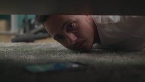 Een jonge kerel vindt een verloren smartphone onder de bank in de woonkamer stock video