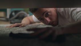 Een jonge kerel vindt een verloren sok onder de bank in de woonkamer stock videobeelden