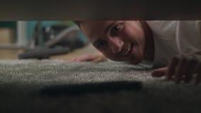 Een jonge kerel vindt een verloren TV onder de bank in de woonkamer ver stock video