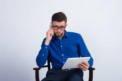 Een jonge kerel zit met tablet en telefoon Stock Foto
