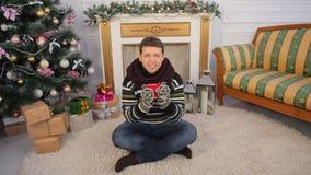 Een jonge kerel zit op de vloer van zijn huis met een mok hete thee Het thema van Kerstmis Royalty-vrije Stock Afbeelding