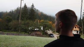 Een jonge kerel zit op een schommeling en bekijkt het bos in de mist stock footage