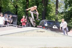 Een jonge kerel zonder een T-shirt die op een springplank, Polen schaatsen, stock foto