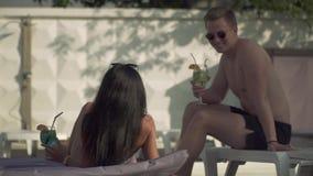 Een jonge kerel in zwembroek en zonnebril communiceert met twee mooie meisjes die in badpakken zitten stock videobeelden
