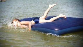 Een jonge kerel zwemt in het overzees op een opblaasbare matras Positieve emoties De hete Dag van de Zomer stock videobeelden
