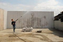 Een jonge kerelspelen met een autowasseretteslang Stock Foto's