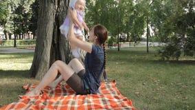 Een jonge kindermeisjezitting op een deken en naar omhoog het werpen van een babymeisje stock footage