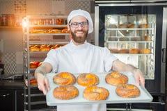 Een jonge knappe bakker die verse ongezuurde broodjes met papaverzaden houden op een dienblad op de achtergrond van een oven en e stock foto's