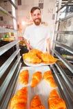 Een jonge knappe bakker houdt hete verse croissants in de handen van een oven stock afbeeldingen