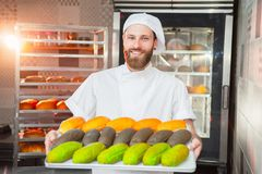 Een jonge knappe bakker houdt kleurrijke verse gebakken goederen op een blad op de achtergrond van de oven royalty-vrije stock foto