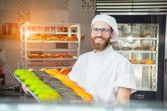 Een jonge knappe bakker houdt kleurrijke verse gebakken goederen op een blad op de achtergrond van de oven stock fotografie