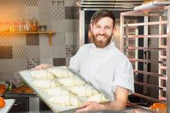 Een jonge knappe bakker houdt ruwe croissants van wit deeg in de handen van een oven Halffabrikaten van deeg royalty-vrije stock foto's