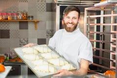 Een jonge knappe bakker houdt ruwe croissants van wit deeg in de handen van een oven Halffabrikaten van deeg stock afbeelding