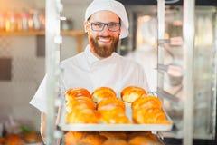 Een jonge knappe bakker met een blad van verse croissants in handen op een bakkerij en ovenachtergrond stock foto
