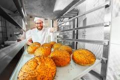 Een jonge knappe bakker neemt verse hete broodjes met papaverzaden van de oven voor de bakkerij stock afbeeldingen