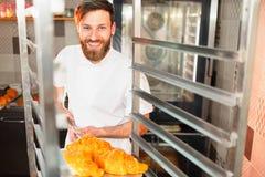 Een jonge knappe bakker neemt verse hete croissants van de oven op een schop stock afbeeldingen