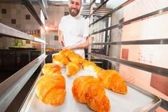 Een jonge knappe bakker neemt verse hete croissants van de oven op een schop royalty-vrije stock afbeelding