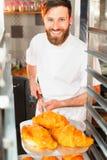 Een jonge knappe bakker neemt verse hete croissants van de oven op een schop stock foto