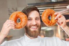 Een jonge knappe bakker toont een smiley van verse ongezuurde broodjes met sesamzaden op de achtergrond van de oven royalty-vrije stock afbeeldingen